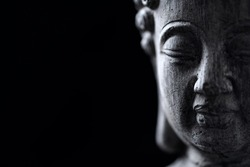 Meditating Buddha Statue isolated on black background. Copy space.
