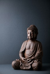 Meditating Buddha Statue on paper background. Copy space.