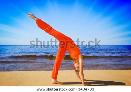 Meditating girl on the beach - stock photo