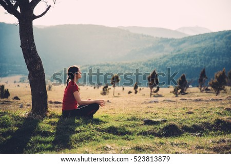 Meditating in nature on a sunny day. Finding inner peace. Practicing yoga. Well-being and healthy lifestyle concept.Enjoying peace and quiet,anti-stress therapy,mindfulness concept.