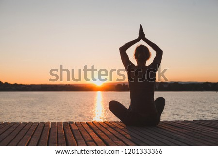 meditation and yoga practice at sunset, silhouette of woman, calmness and harmony #1201333366