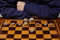Meditation at the chessboard. The chess player hands lie on a polished chess table. A row of shelled walnuts is placed on the board