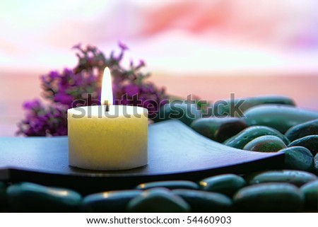 Meditation candle burning on a wood dish over a bed of stones with lavender flowers for a spiritual meditative Zen experience