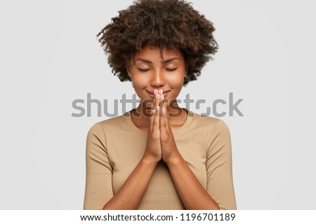 Meditation concept. Beautiful young black woman stands in meditative pose, enjoys peaceful atmosphere, holds hands in praying gesture, isolated over white background, has sense of inner peace