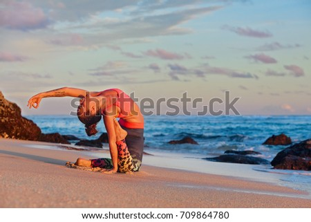 Stock Photo Meditation on sunset sky background. Young active woman sit in yoga pose on sand beach, stretching to keep fit and health. Healthy lifestyle, outdoor fitness, sports activity on summer family holiday.