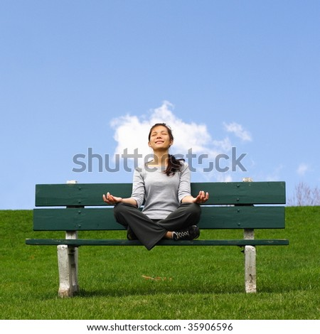 Meditation outside with head in the clouds. Beautiful mixed asian / caucasian young woman thinking in park.