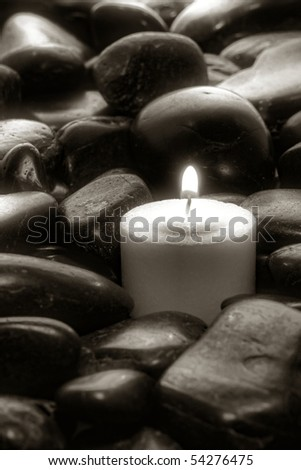 Meditation votive candle burning in a bed of stones in artistic black and white