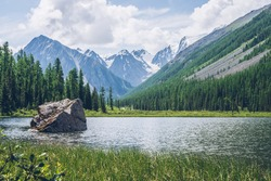 Meditative view to beautiful lake with stone in valley on snowy mountains background. Scenic relaxing green landscape with big mossy stone in mountain lake. Alpine lake with ripples on water surface.