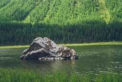 Meditative view to big mossy stone closeup in beautiful green lake on forest mountain background. Atmospheric alpine green landscape with big stone and ripples in lake surface. Scenic relaxing place.