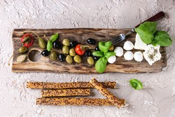 Mediterranean appetizer antipasti board with green black olives, feta cheese, mozzarella, capers, pepper, basil with grissini bread sticks over beige concrete texture background. Top view with space