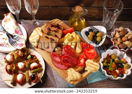 mediterranean appetizers and antipasti with olives,mozzarella,dried tomatoes on wooden table