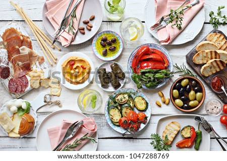 Mediterranean appetizers table concept. Diner table with antipasto selection: grilled vegetables, cured meat and salami,  jamon, olives, cheese, hummus and roasted bread.  Overhead view. Сток-фото ©