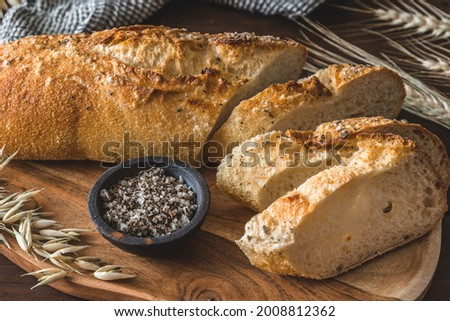 Mediterranean baguette with herbes and sel de mer on a wooden board Stock fotó ©