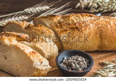 Mediterranean baguette with herbes and sel de mer on a wooden board, closeup Stock fotó ©