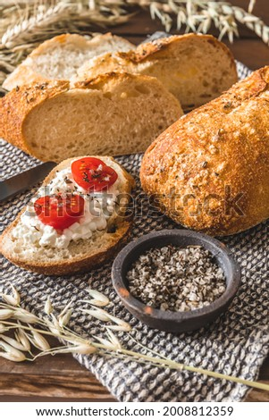Mediterranean baguette with herbes and sel de mer, one slice with cream cheese and tomatoes, vertical Stock fotó ©