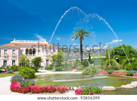 mediterranean garden with fountain, colorful flowers and blue sky. Near Nice, Cote d\'Azur, France