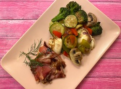 Mediterranean grilled vegetable platter. With raw ham, zucchini, tomatoes, broccoli, onions, mushrooms, bell pepper, herbs and balsamic vinaigrette.