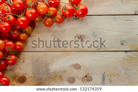 Mediterranean ingredients: ripe tomatoes on rustic wood table. Plenty of copyspace, perfect for a menu. Landscape orientation.