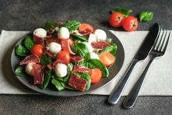 Mediterranean Kitchen. Fresh salad with arugula, mozzarella, prosciutto and capers on a dark background.
