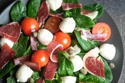 Mediterranean Kitchen. Fresh salad with arugula, mozzarella, prosciutto and capers on a dark background close-up top view.