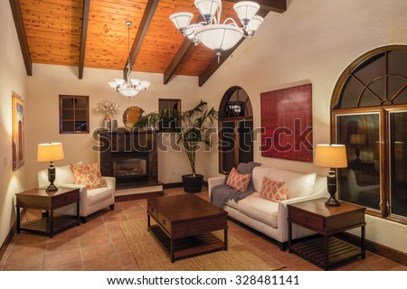 Mediterranean living room at night with beige walls, sofa, sectionals, wooden stands, fireplace place, coffee table and wooden ceiling.