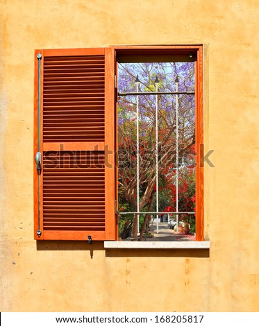 Mediterranean open window with shutters and blossoming trees and bushes on the small street outside