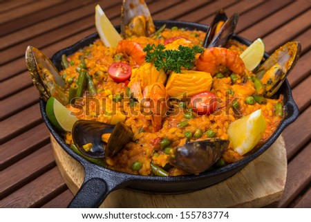 mediterranean paella with seafood in frying pan on wooden board