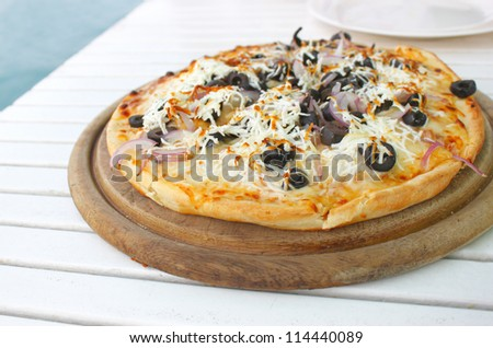 mediterranean pizza on wooden round plate