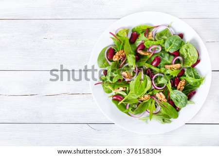 Mediterranean red beans salad with mix of lettuce leaves and walnuts on a white dish on a wood table with blank space left, italian style, close-up #376158304