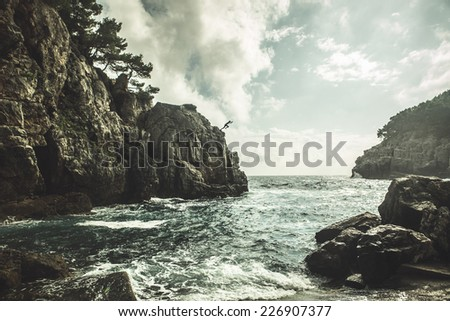 Mediterranean rocky shores and landscape - Odysseus cave on island Mljet near Dubrovnik, tourist attraction, Croatia. Young man jumping from the cliff in distance. Cliff jumping recreation on seaside #226907377
