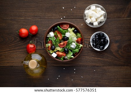 Mediterranean salad with olives and feta in bowl on rustic wooden table. Top view.