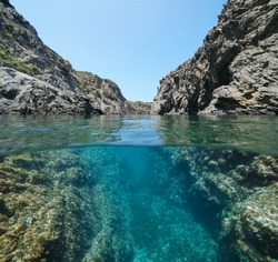 Mediterranean sea rocky coast with a passage between rocks, split view over and under water surface, Spain, Costa Brava, Catalonia, Cap de Creus