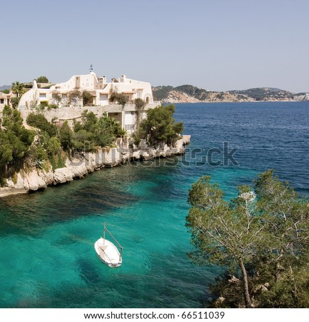 Mediterranean seascape with clear and transparent water, some coastal pines, rocks, edifice and anchored small white boat. Mountainous horizon in the background.  Coast of Mallorca (Cala Fornell)