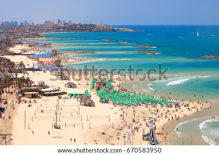 Mediterranean seaside of Tel Aviv. Beaches and old embankment (before restoration) view. Ancient Arab city of Jaffa or Yafo - the oldest part of Tel Aviv - Yafo on the horizon. Israel.