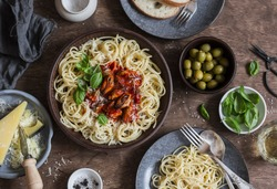 Mediterranean style lunch. Spaghetti with canned mussels and tomato sauce. On a wooden table, top view. Flat lay