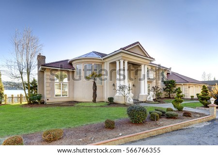 Mediterranean style luxury waterfront home features Low-pitched tile roof, stucco walls, columned porch and arch motifs. Well-manicured landscape design creates perfect curb appeal. Northwest, USA   #566766355