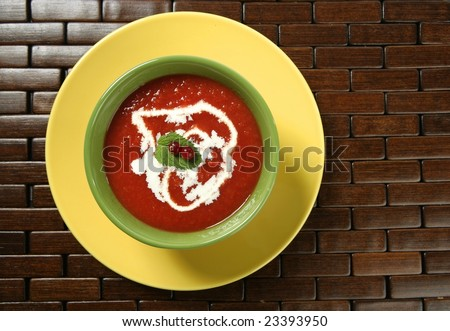 Mediterranean tomato soup with basil and redcurrant  in a colorful green dish over wood