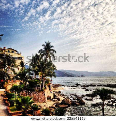 Mediterranean view with palm trees, terraces, mountains and streaky cirrus clouds.