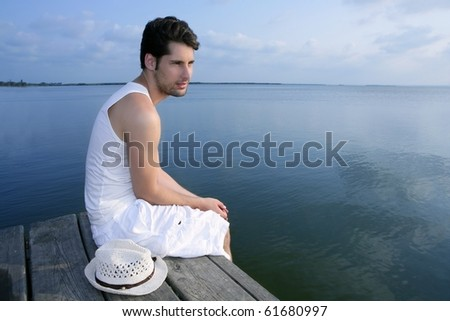 Mediterranean young latin man relaxed on wood pier white hat