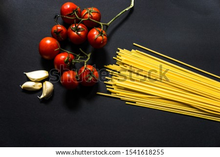 Mediterrannean cuisine and ingredients. Spaghetti with ingredients for cooking pasta on a black background