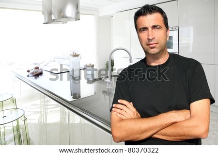 Medium age man in modern kitchen interior portrait crossed arms [Photo Illustration]