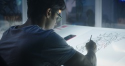 Medium close-up of a young graphic designer drawing concept art for video game