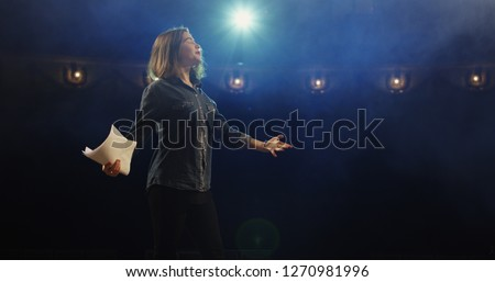 Medium close-up of an actress rehearsing a monologue in a theater while holding her script