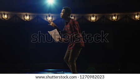 Medium close-up shot of an actor performing a monologue in a theater while holding his script Foto stock ©
