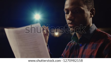 Medium close-up shot of an actor performing a monologue in a theater while holding his script