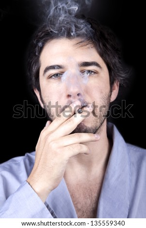 Medium closeup of an adult man (30 years), which  appears to be quite a bum, giving the camera a numb gaze, concentrated in smoking a marijuana spliff (aka reefer; joint). Isolated on black background