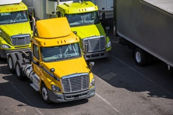 Medium duty professional freight powerful rigs industrial diesel semi trucks with refrigerated semi trailers standing on the tight warehouse street parking lot waiting for the next delivery