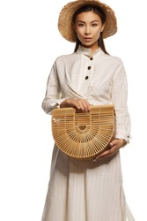 Medium full shot of a young Asian lady with a sandybrown bamboo handbag in her hands. The girl is wearing a white striped tunic dress with steel buttons and a straw hat.