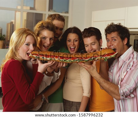 Medium group of people sharing large sandwich
