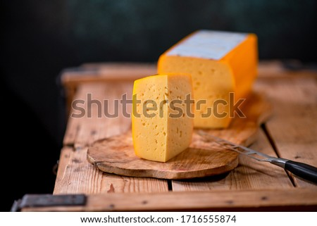 Medium hard cheese gouda edam on wooden board on sunlight table traditional table texture side view